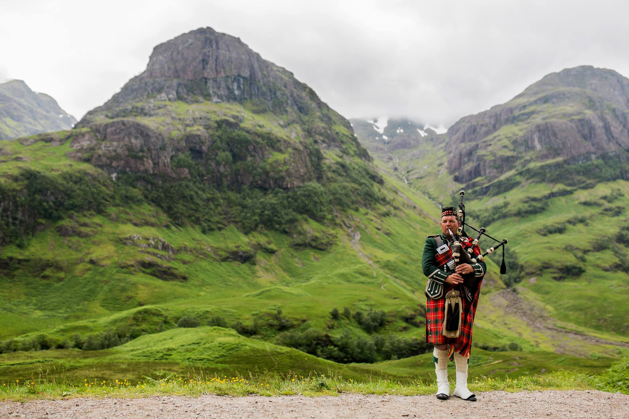 Man in kilt playing bagpipes in hills