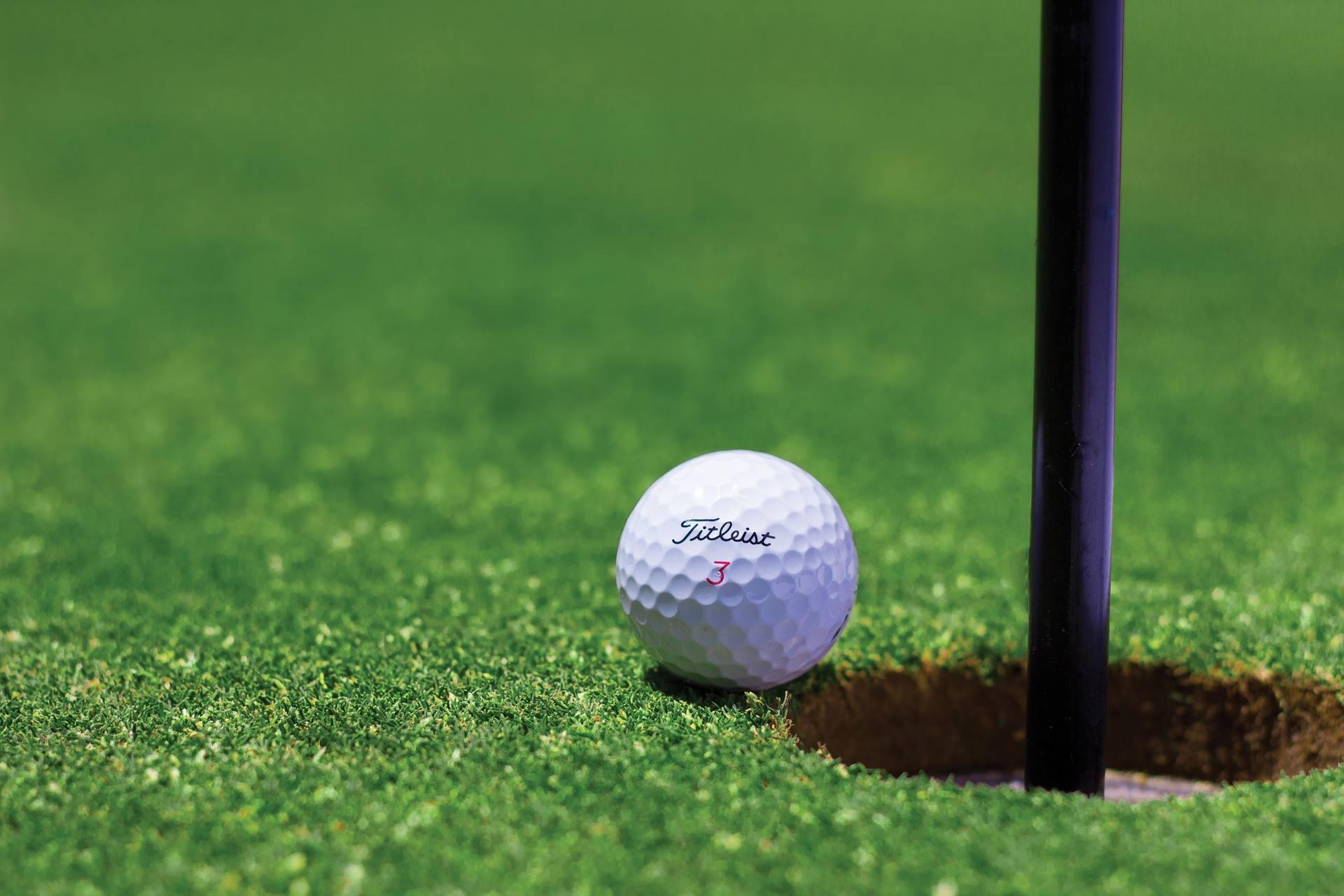 Titleist golf ball near hole