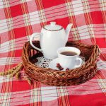 Teapot and teacup on tray and tartan plaid tablecloth